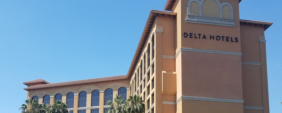 """The exterior of a hotel with large windows on the upper floor and """"Delta Hotels"""" on the side of the building"""