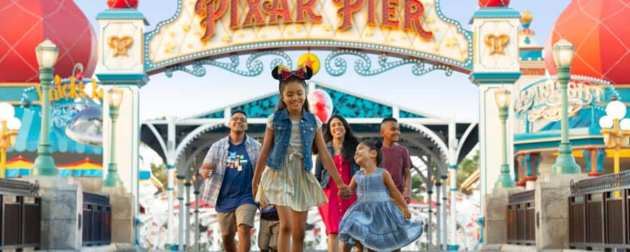 2 little girls hold hands with their family behind them as they walk in front of Pixar Pier