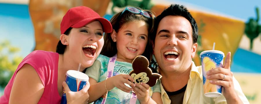 A husband and wife smile as they pose cheek-to-cheek with their daughter who holds a Mickey cookie