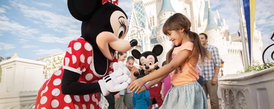 Outside Sleeping Beauty Castle, Minnie greets a girl while Mickey entertains the girl's family