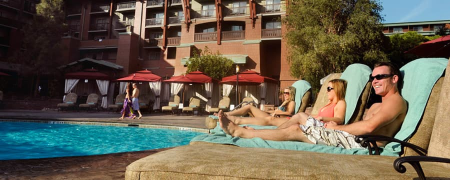 Three Guests in bathing suits sit poolside in lounge chairs at Disney's Grand Californian Hotel & Spa