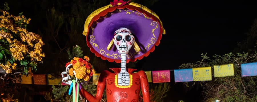 Un esqueleto festivo con una calavera de azúcar mexicana pintada a mano, un gran sombrero y un ramo de flores