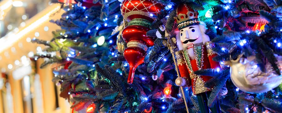 illuminated christmas lights assorted glass bulbs and a nutcracker ornament adorn a tree - When Does Disneyland Decorate For Christmas 2017