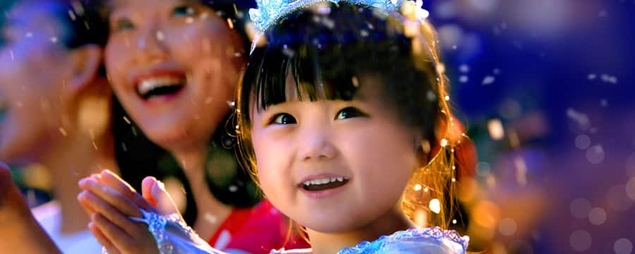A little girl and her mother smile in amazement and joy as snow falls