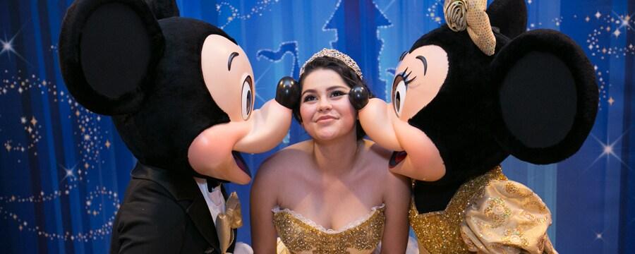Una joven sonriente con traje de quinceañera se inclina para que Mickey y Minnie Mouse le puedan besar cada una de las mejillas