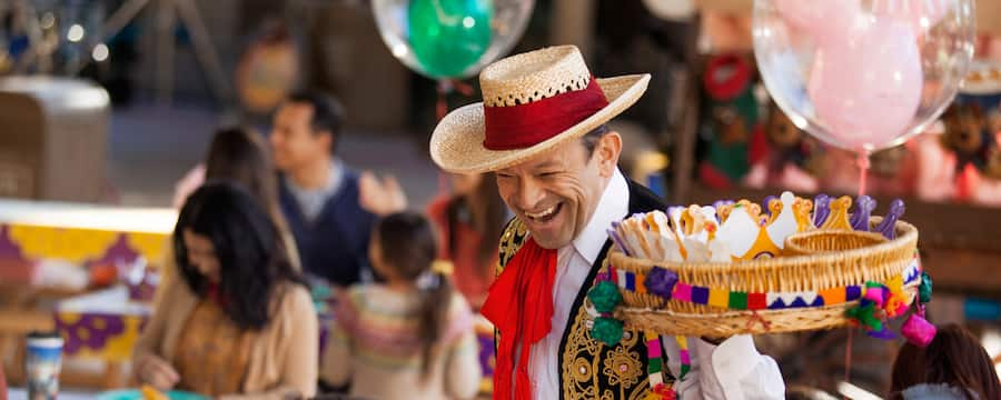 At a 3 Kings Day celebration, a man in festive Latin American dress carries a tray containing paper crowns