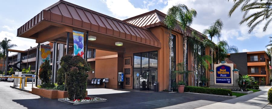 The carport overhang and entrance to Best Western Plus Stovall's Inn accented with palm trees