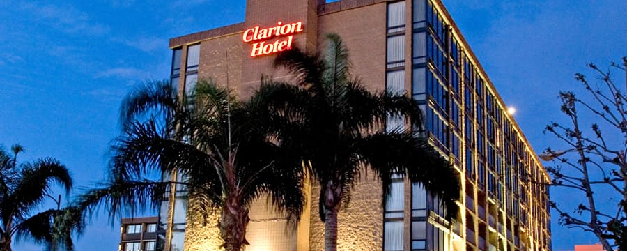 Palm trees accent the ground around the Clarion Hotel Anaheim Resort lit up at night