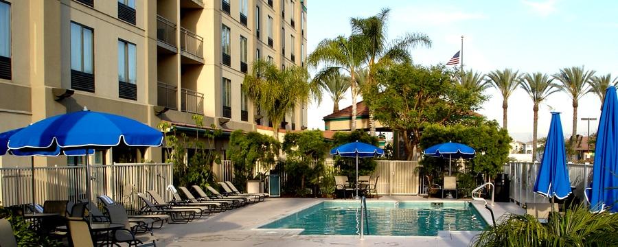 Camastros y sombrillas bordean la piscina en Hampton Inn & Suites