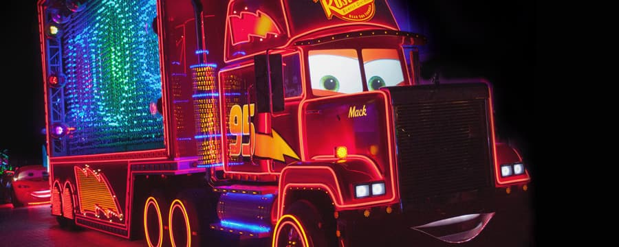 Covered in neon lights and an illuminated Rust ease logo, the Mack truck from Cars cruises by