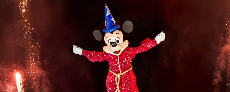 Sorcerer Mickey smiling while sparks fly through the evening sky during a performance of Fantasmic!