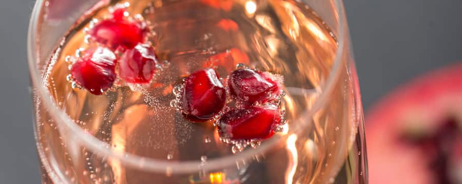 Pomegranate fruit garnishes chilled sparkling champagne in a tall fluted glass