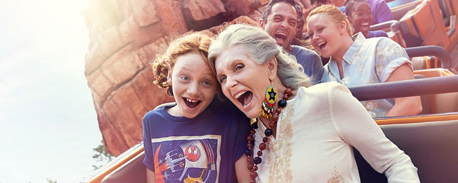A grandmother and granddaughter scream with delight on a Walt Disney Resort roller coaster