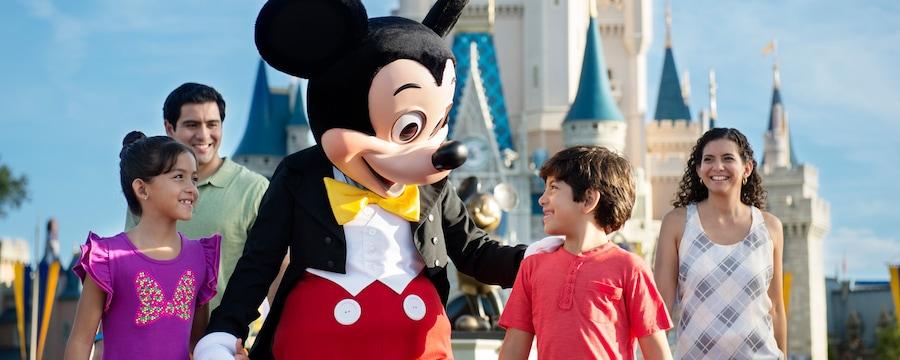 O Mickey Mouse caminhando com 2crianças e seus pais perto do Cinderella Castle no Magic Kingdom Park