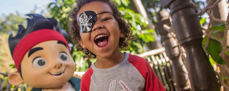 Jake parado detrás de un niño sonriente con un parche en el ojo