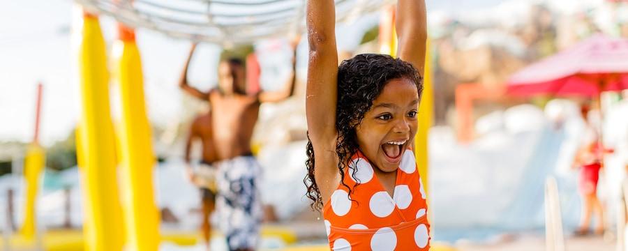 Une jeune fille portant un maillot de bain sourit dans un parc aquatique