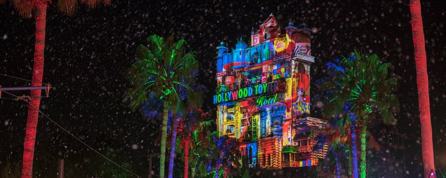 The Hollywood Tower Hotel with projections of toys on it near palm trees and stars made of lights