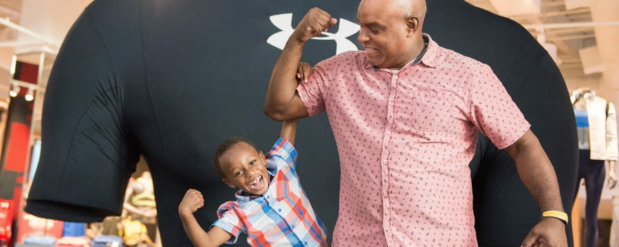 A young boy makes a muscle as he hangs from his dad's bicep in front of a larger than life Under Armour T shirt