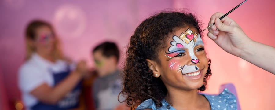 A smiling young girl sits in a chair wearing face paint