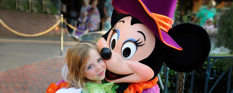 A young female Guest dressed as a Disney Fairy smiles while meeting a Halloween-themed Minnie Mouse