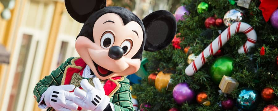 Mickey Mouse dressed in festive holiday clothing while standing next to a decorated Christmas tree