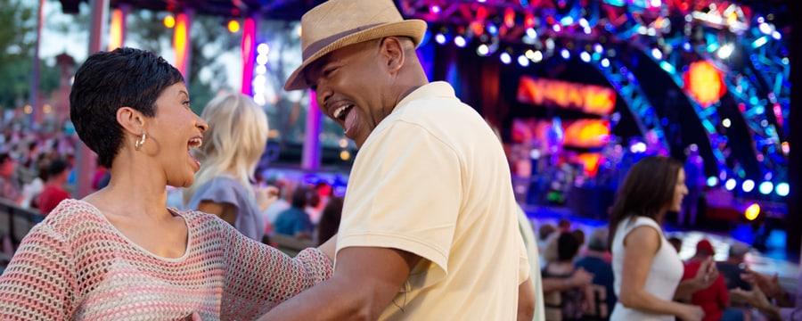 Una mujer y su esposo sonríen y bailan durante un espectáculo de música en vivo de Disney on Broadway