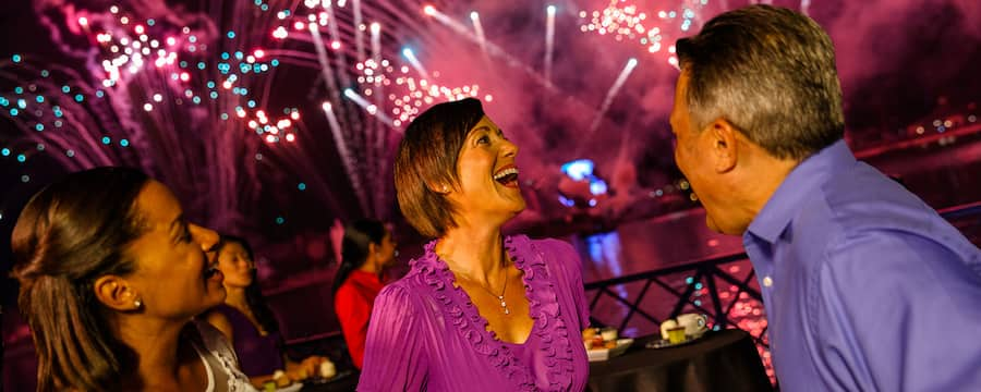 Two women and a man reacting excitedly to a fireworks display as they enjoy beverages and dessert