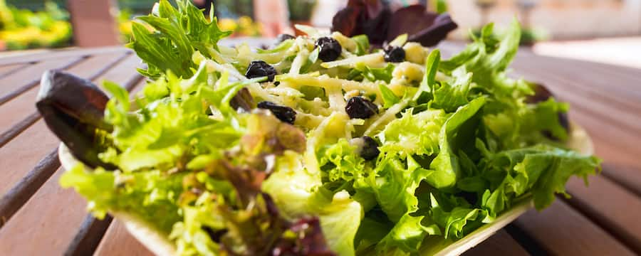 Una festiva ensalada de hojas verdes mixtas decorada con moras, servida sobre una mesa de pícnic de madera