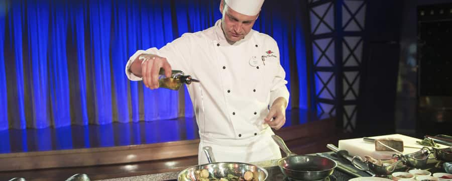 A chef in a demonstration kitchen pours oil into a pan while sautéing scallops with vegetables