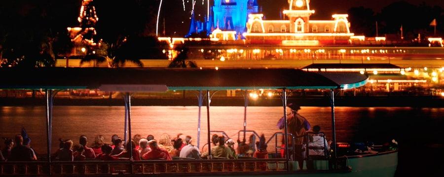 Espectadores en un bote observan el Cinderella Castle iluminado de color púrpura y los fuegos artificiales de fondo