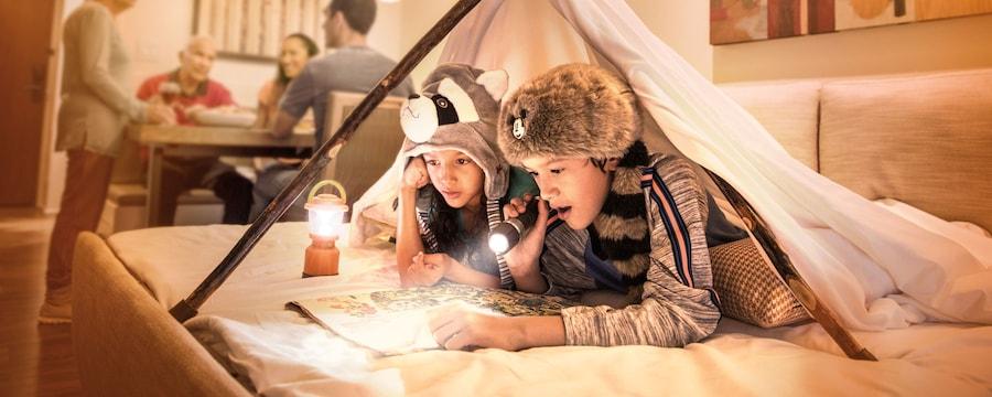 Dos niños con novedosos gorros inspirados en Frontierland leen un mapa con una linterna y un farol pequeño debajo de un tipi temporal en la cama de su hotel mientras un grupo de adultos está reunido alrededor de una mesa de comedor