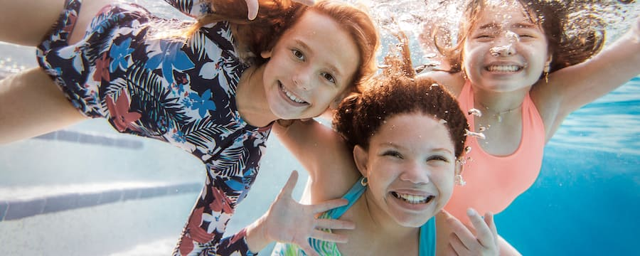 Three girls smiling underwater while swimming in a pool at a Walt Disney World Good Neighbor Hotel