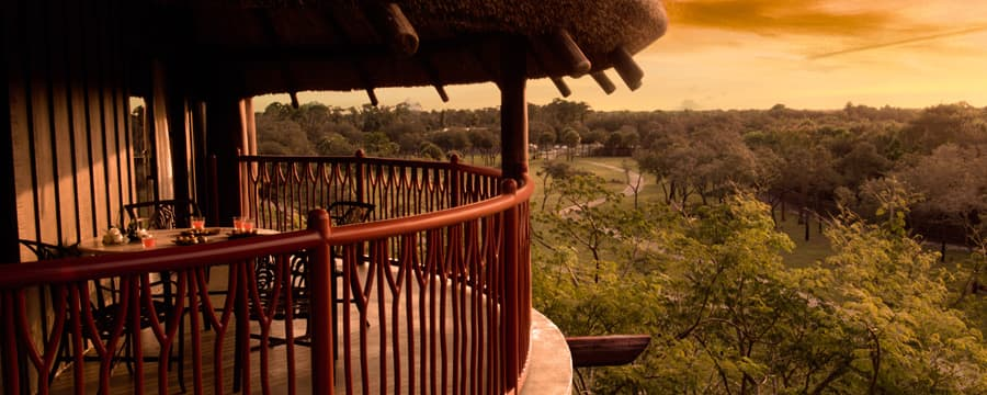 Sob o telhado de palha, uma sacada com mesa e cadeiras contempla a savana do resort ao pôr do sol