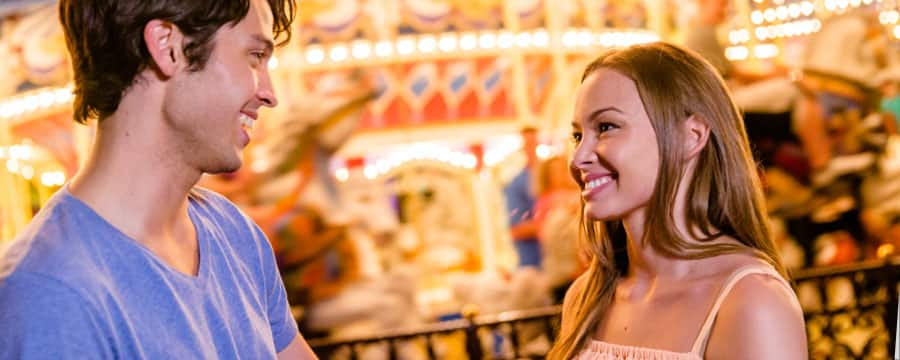 A smiling young couple look at each other while standing near a brightly lit carousel