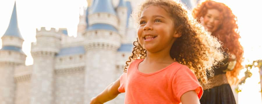Princess Merida, from the film Brave, watches a curly haired little girl twirl near Cinderella Castle