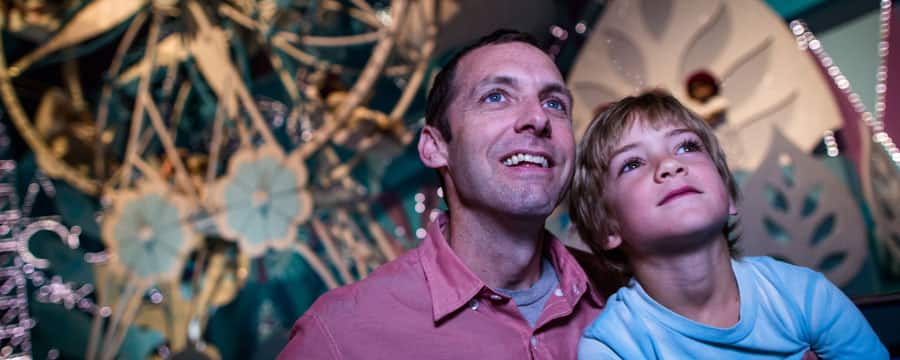 Amazed at the magical scenes, a boy and his dad ride through its a small world at Magic Kingdom Park