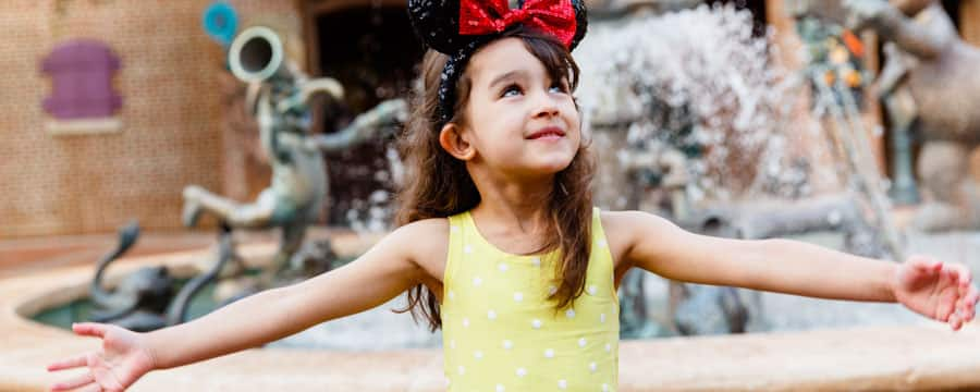 Wearing a sequined Minnie ear headband, a little girl stands by the fountain outside Muppet Vision 3 D