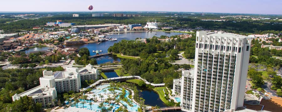 A resort with buildings, a lake, a pool area, trees, a marina and a hot air balloon