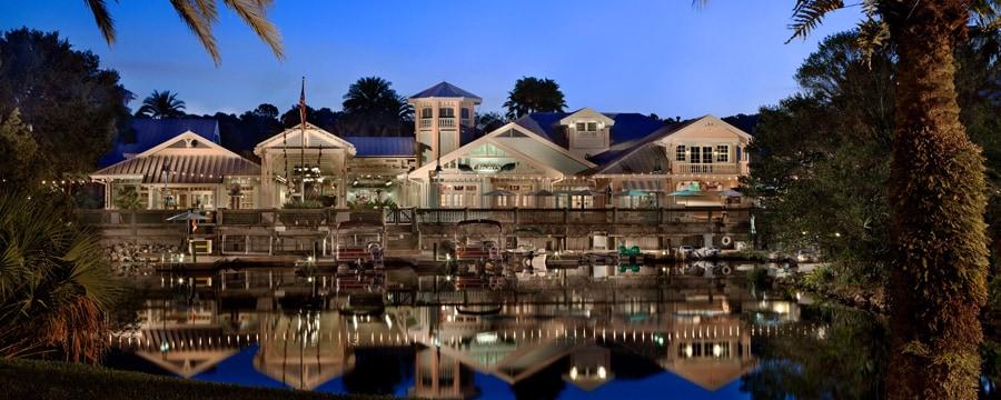 Vista do Disney's Old Key West Resort em frente à água, iluminado à noite