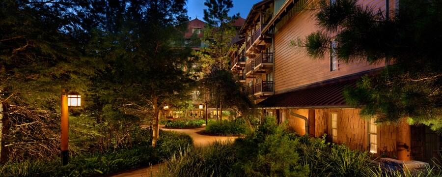 El camino bordeado de árboles hacia la villa en Disney's Wilderness Lodge, iluminado por la noche