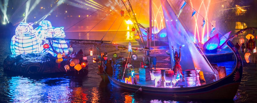 A storyteller dressed in a traditional Asian costume stands on a boat with hanging lanterns while 3 large owl figures occupy a barge nearby