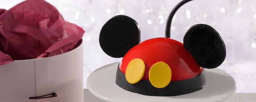 Un pastel domo con forma de Mickey Mouse en un pedestal, cerca del elegante empaque con forma de caja de sombrero de Amorette