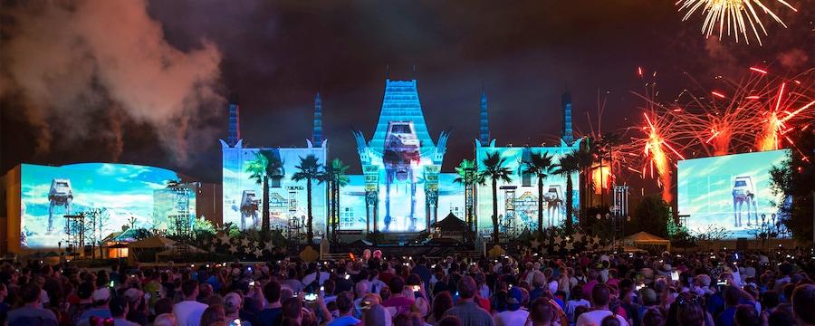 Visitantes observan el Star Wars Galactic Spectacular frente al Grauman''s Chinese Theatre iluminado, con efectos de última tecnología de vehículos AT-AT proyectados en el exterior