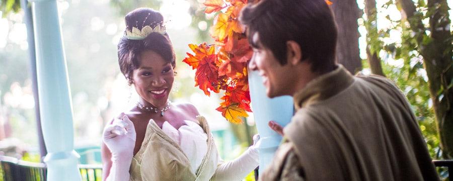 Princess Tiana y Prince Naveen bajo una glorieta con flores