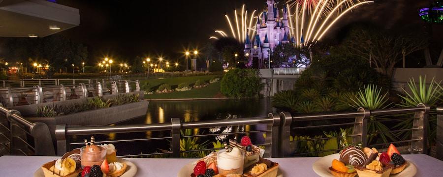Postres en exhibición en Tomorrowland Terrace Restaurant mientras los fuegos artificiales estallan sobre Cinderella Castle