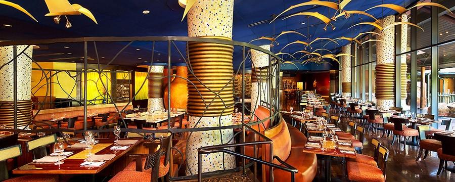 Área de comidas con muebles de madera oscuros iluminado por lámparas en forma de aves
