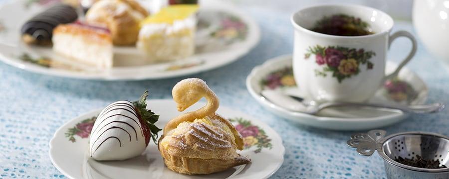 Fraise trempée dans le chocolat blanc, scones en forme de cygne et thé noir sur un service à thé anglais fleuri en porcelaine.