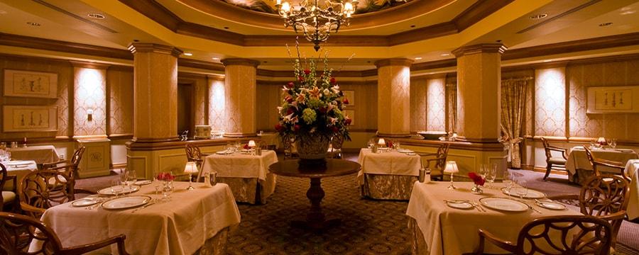 Un resplendissant bouquet repose sous la lueur d'un chandelier au cœur d'une élégante salle à manger