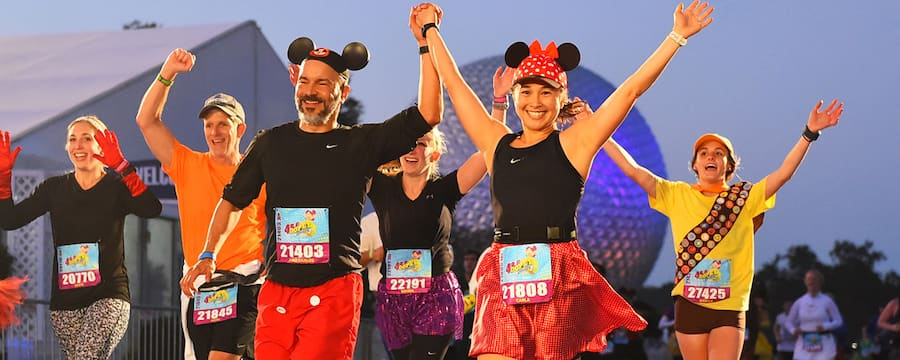 A couple raises their clasped hands while participating in a runDisney event